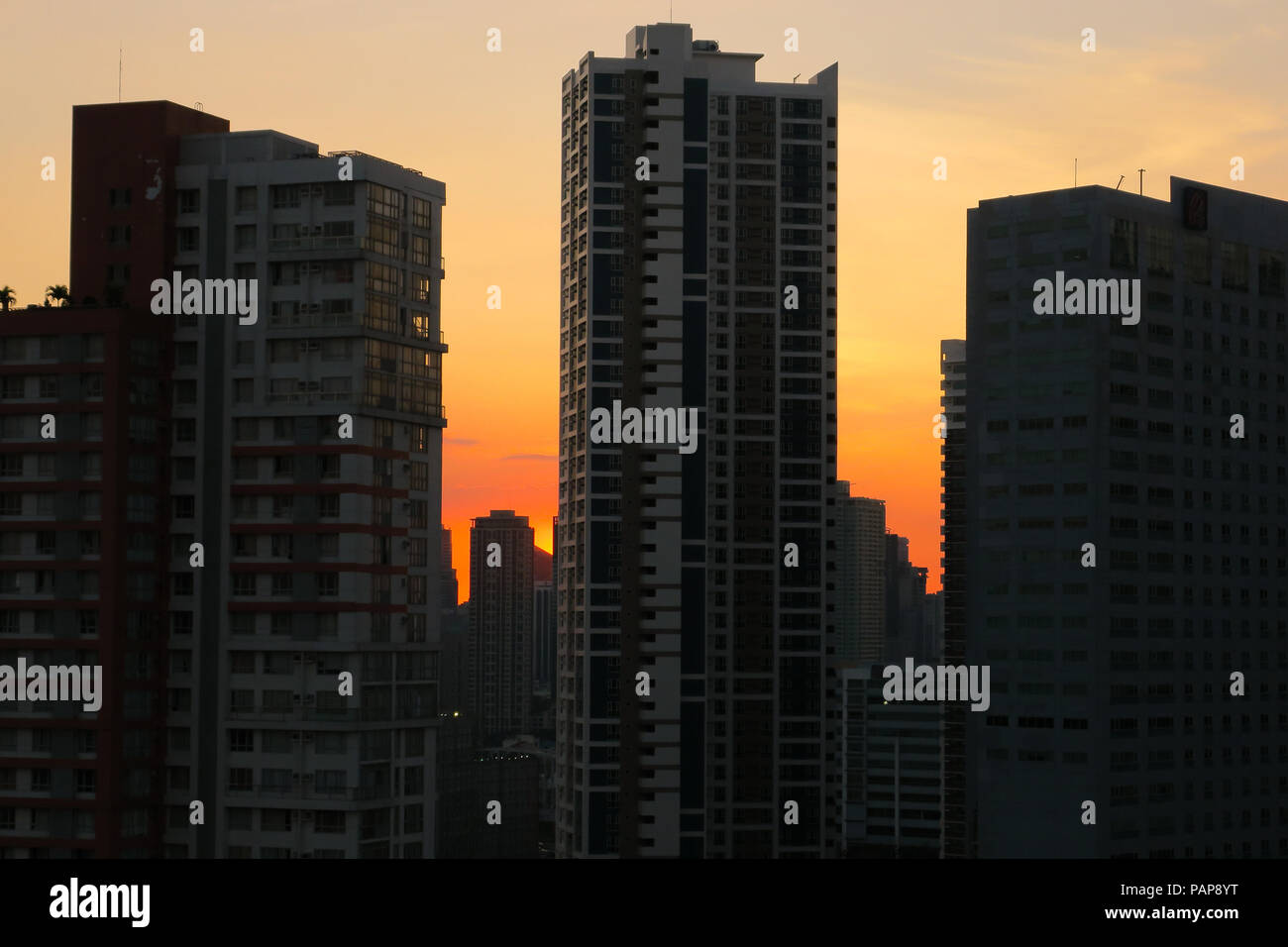 Tall buildings detail with stunning orange pollution sunset in metro Manila, from Kapitolyo, Pasig - Philippines - Stock Image