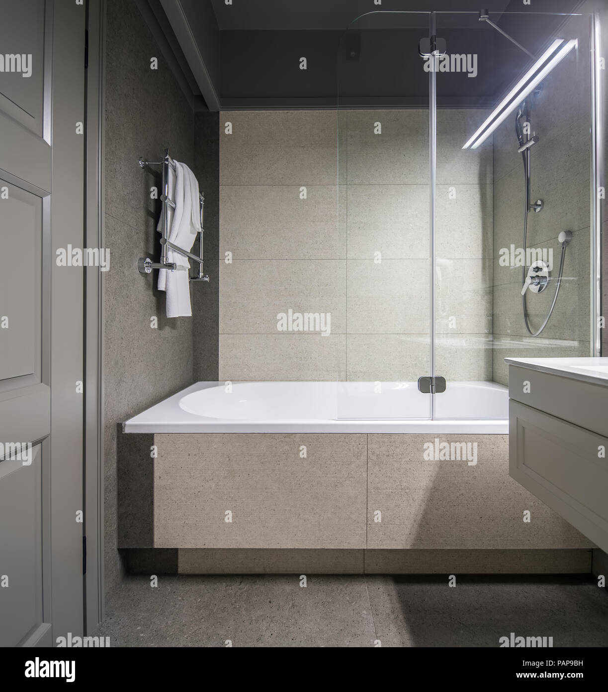 Stylish bathroom with light tiled walls. There is a white bath with ...