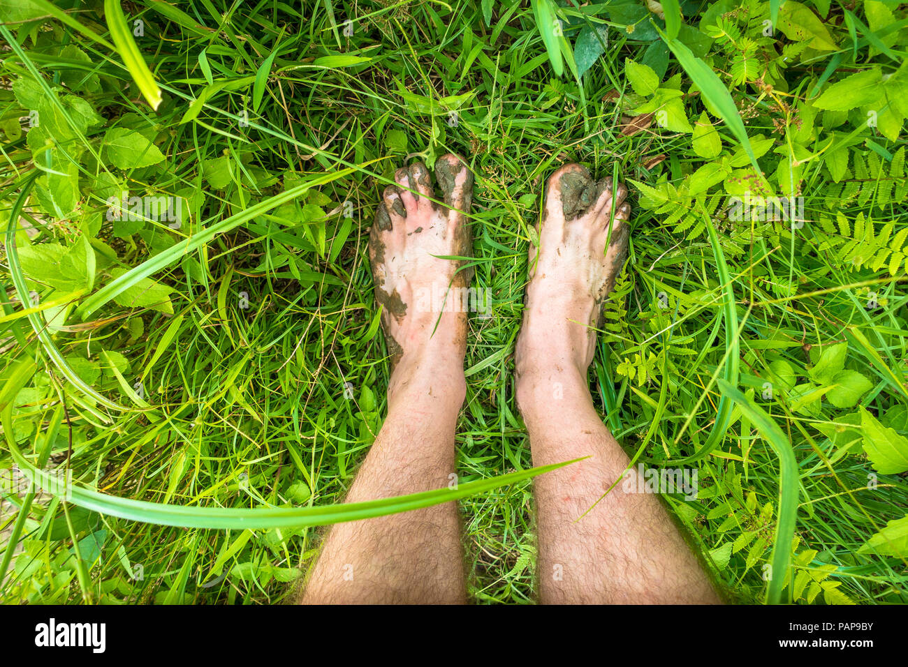 Muddy toes and feet while trekking barefoot through jungle plants in Sabang, Puerto Princesa - Palawan - Philippines - Stock Image