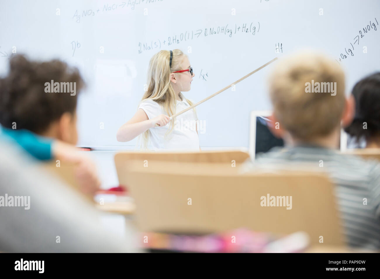 Schoolgirl explaining formula at whiteboard in class - Stock Image