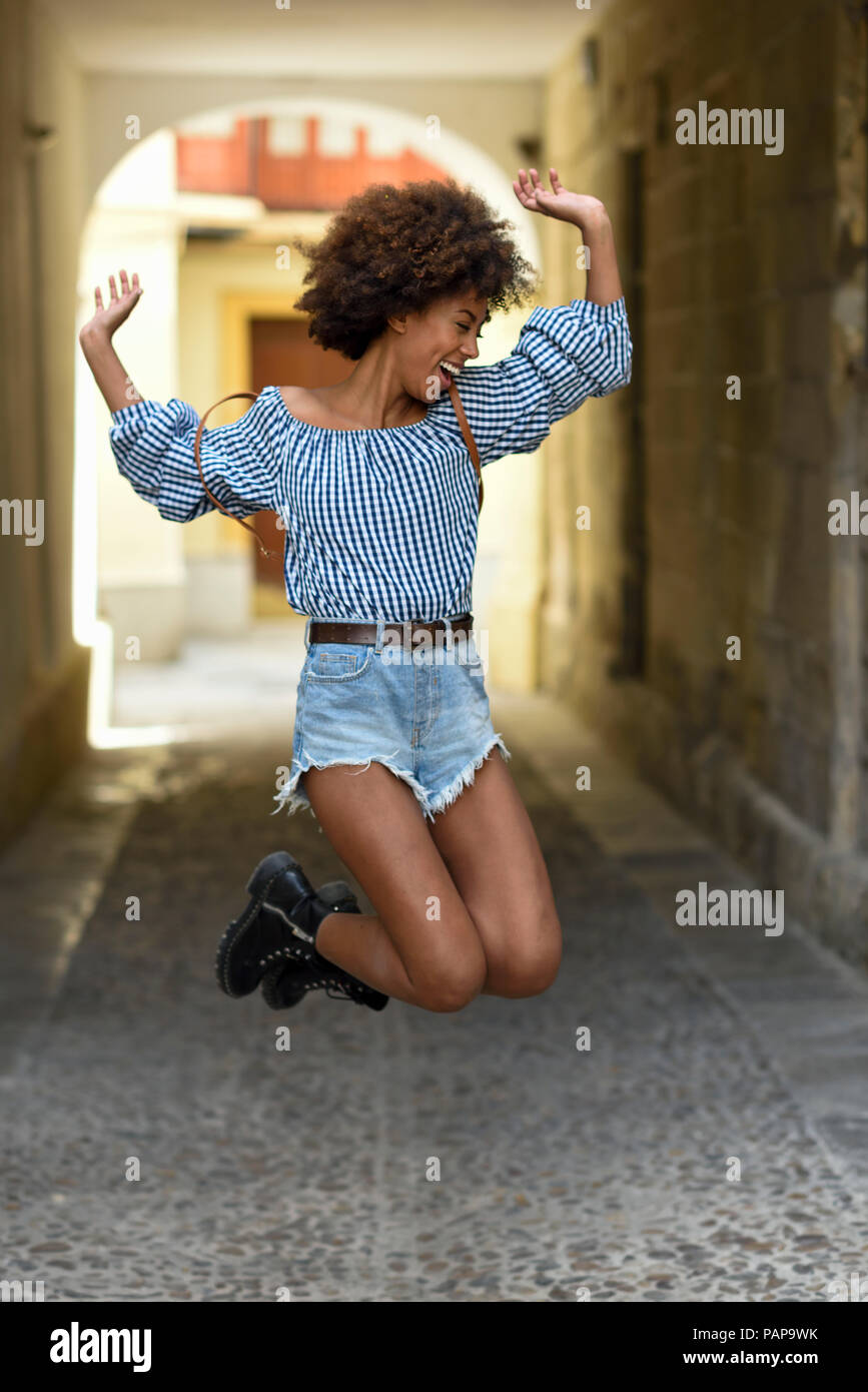 Laughing young woman jumping in the air - Stock Image