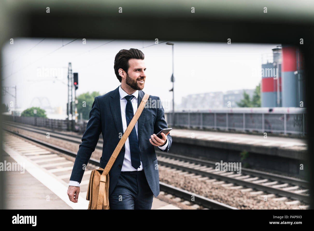 Smiling businessman with cell phone walking at the platform - Stock Image