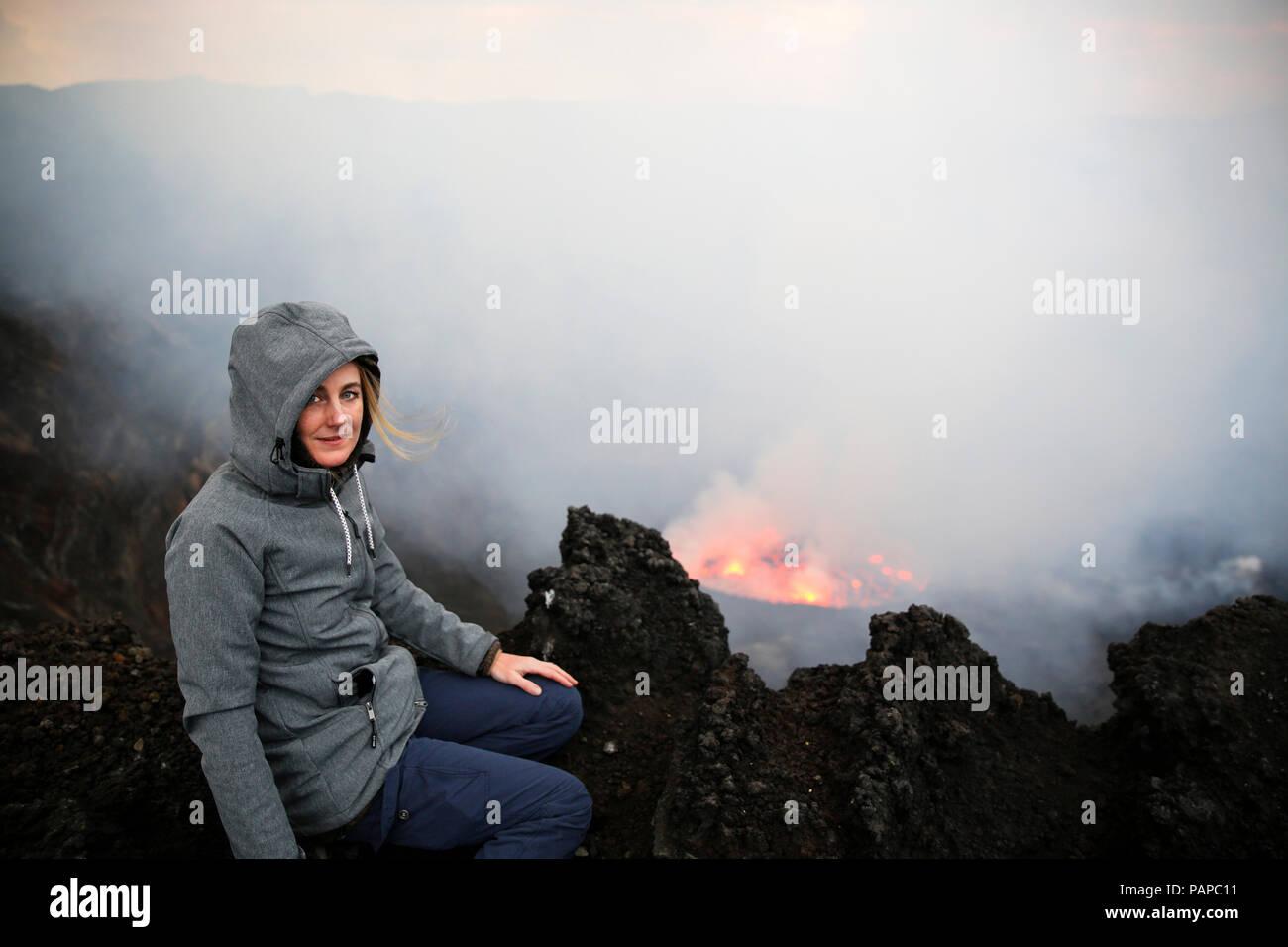 Africa, Democratic Republic of Congo, Virunga National Park, Woman sittiing over Nyiragongo volcano crater - Stock Image