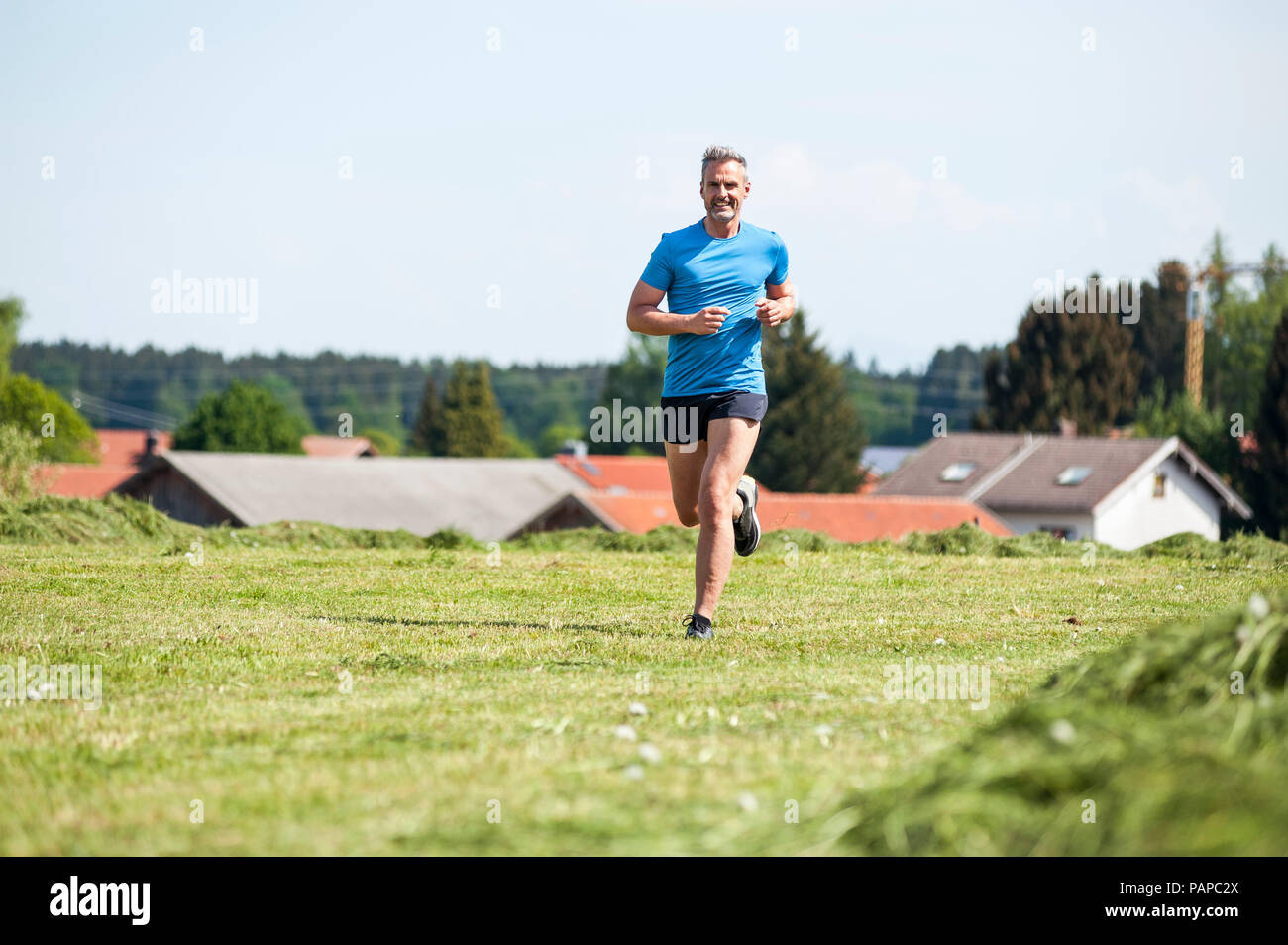 Mature man running on meadow - Stock Image