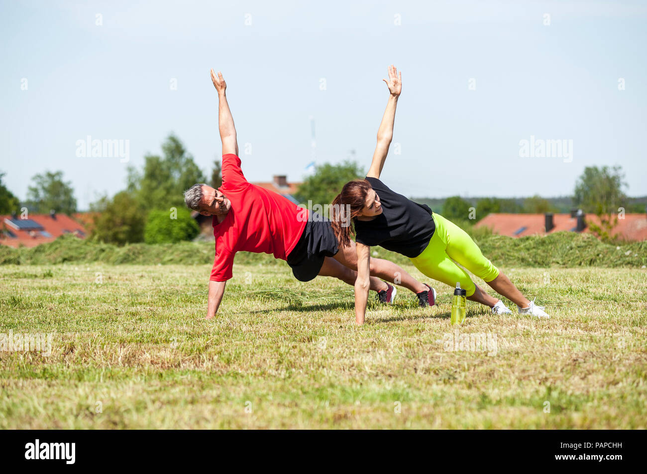 Couple doing side plank exercise on meadow - Stock Image