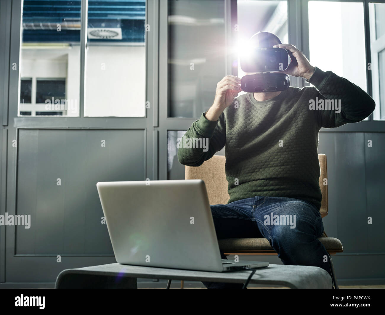 Man working with VR glasses and laptop - Stock Image