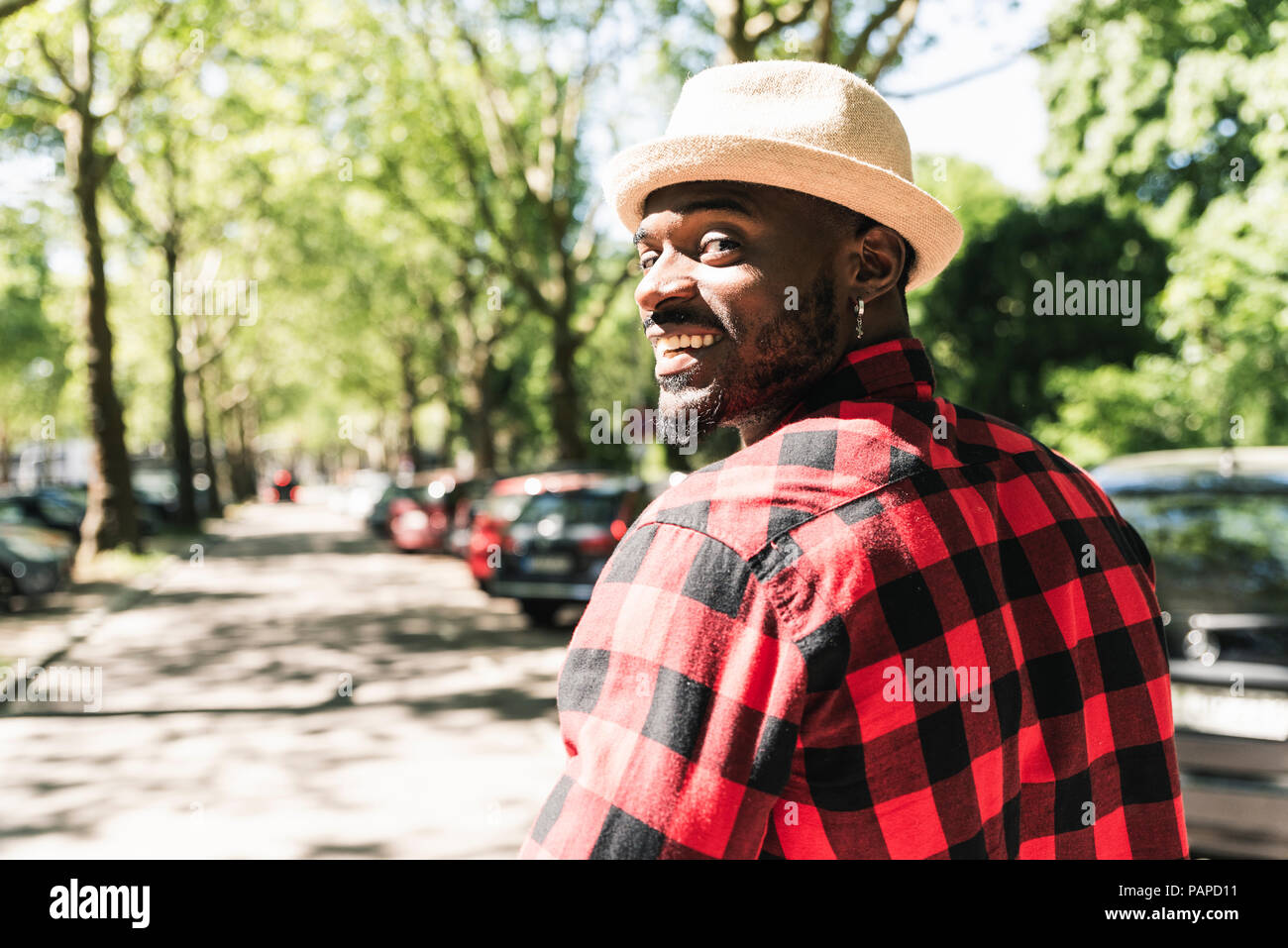 Cool young man walking in the city, portrait - Stock Image