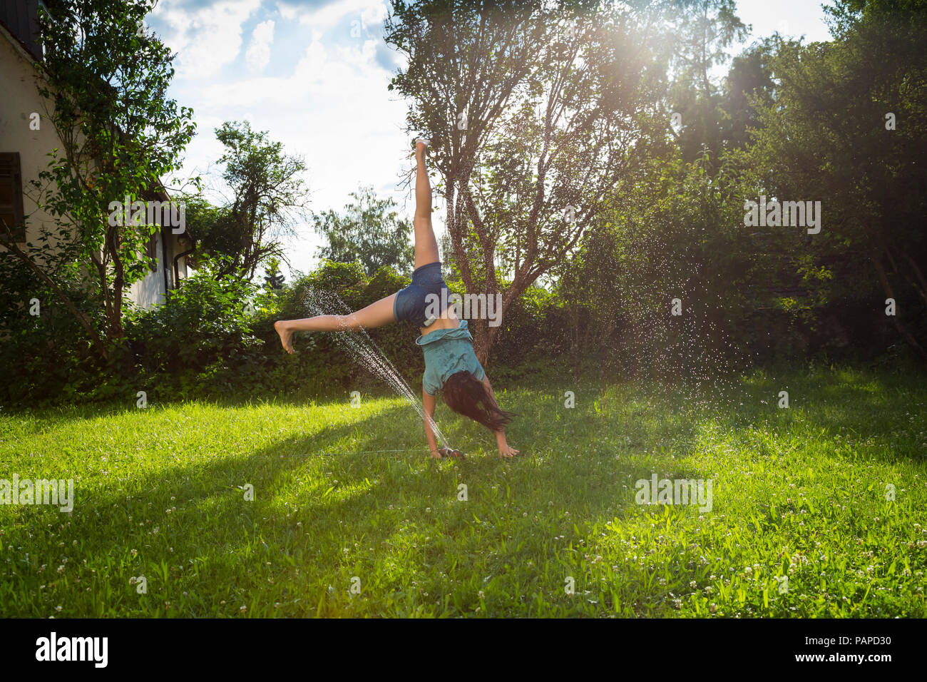 Girl having fun with lawn sprinkler in the garden - Stock Image