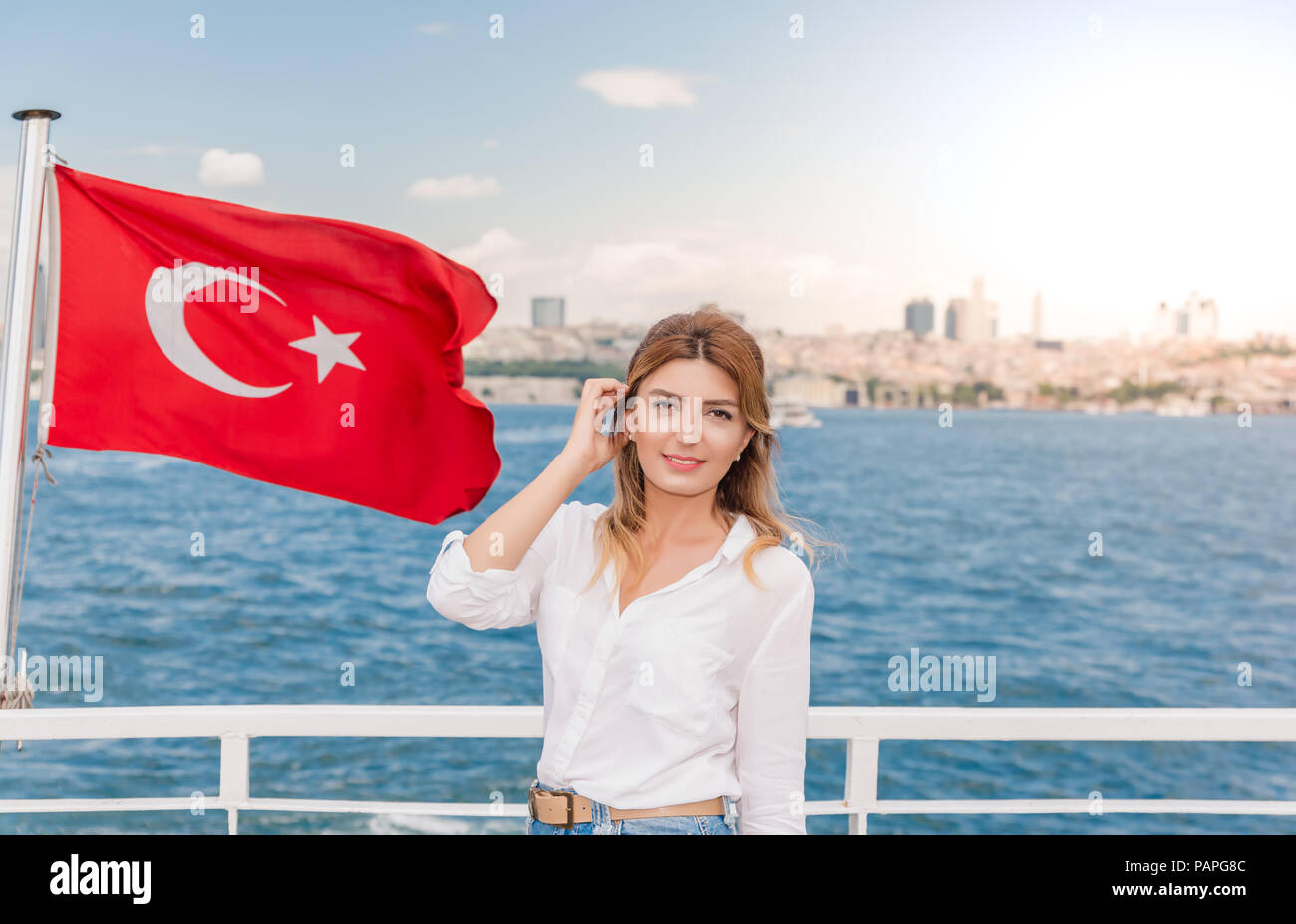 Beautiful woman travels with ferry between Asia and Europe with view of Turkish flag.Istanbul,Turkey Stock Photo