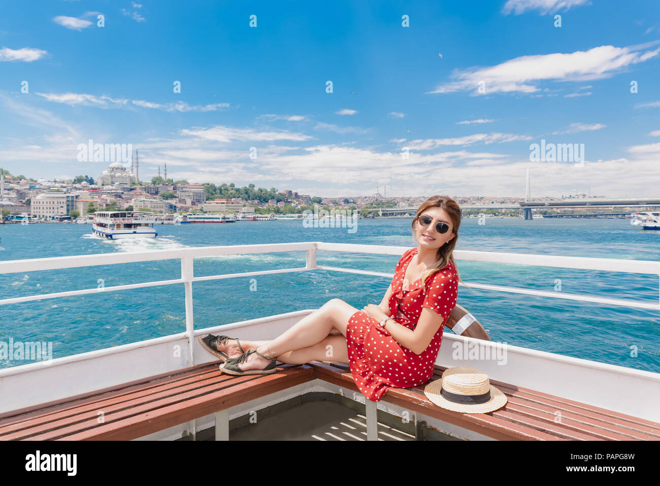 Beautiful woman in red dress sits on a ferry with landscape view of Istanbul on background. Stock Photo