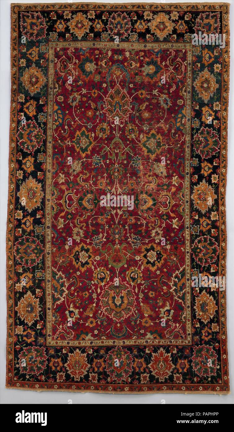 'Floral and Cloudband' Carpet. Dimensions: L. 97.5 x W. 56.25 in. (247.65 x 142.87 cm). Date: 17th century.  This type of carpet is characterized by a weft structure with four plies and a dense knot count, which explain the tightness and heaviness of the rug. Common Persian motifs are usually knotted in a rich palette with two to three different tones per color. Starting from the center, cloudbands, peonies, lotuses, and other flowers develop in spiral-like movements and are arranged following vertical and horizontal symmetrical axes. Contrasting ground colors--rich red and dark blue--accentua - Stock Image