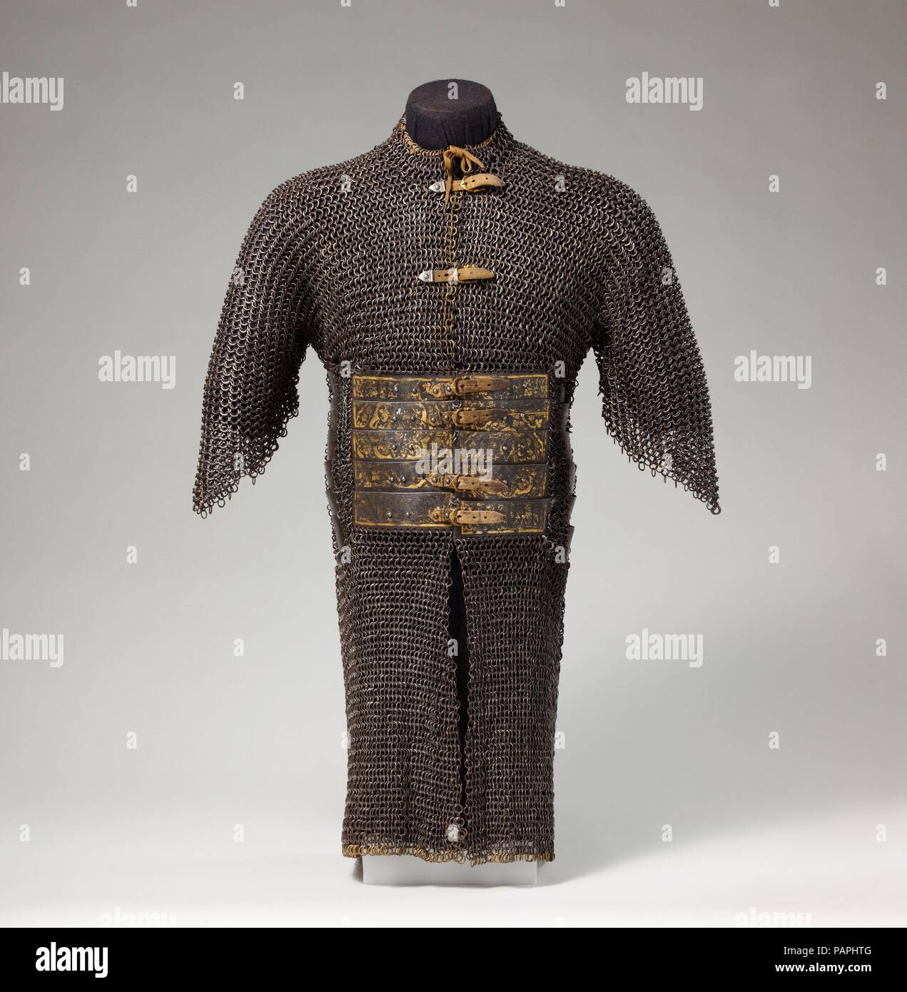 Shirt of Mail and Plate. Culture: Iranian or Turkish. Dimensions: H. 39 1/4 in. (99.7 cm); W. at shoulders 19 in. (48.26 cm); L. of metal plate at waist 8 1/2 in. (21.59 cm); W. of metal plate at waist 10 1/2 in. (26.67 cm); Wt. 25 lb. 10 oz. (11.61 kg). Date: 15th-16th century.  Acording to a Venetian ambassador writing in about 1478, the Ak-Koyunlu (White Sheep Turkoman) wore armor of 'iron in little squares and wrought with gold and silver tacked together with small mail.' Armor of this type seems to have been used throughout eastern Anatolia, Persia, and the Caucasus. This example is inscr - Stock Image