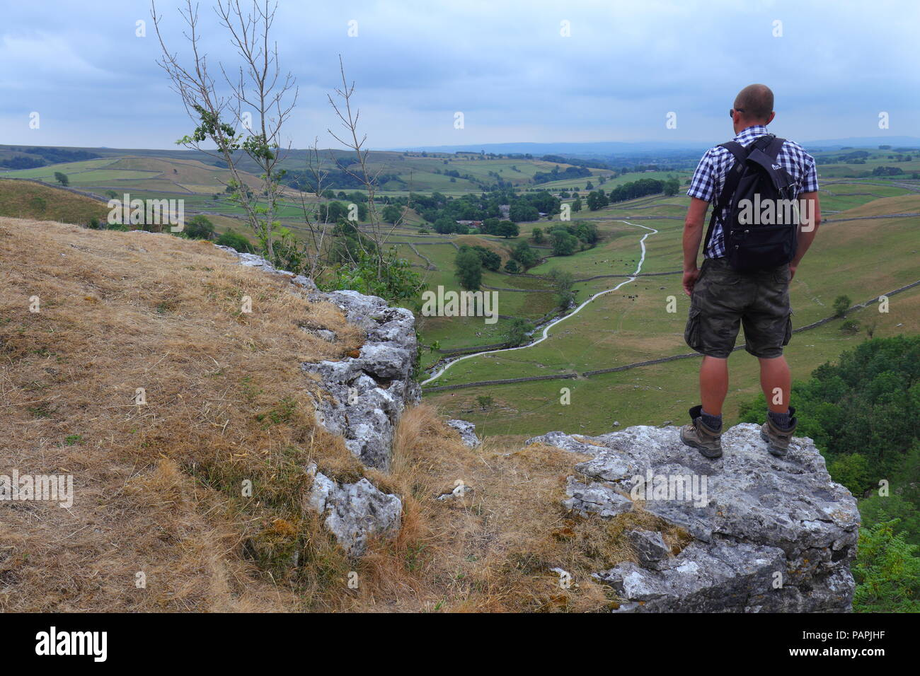 A tourist takes in the beautiful scenery of the Yorkshire Dales from the top of Malham Cove - Stock Image