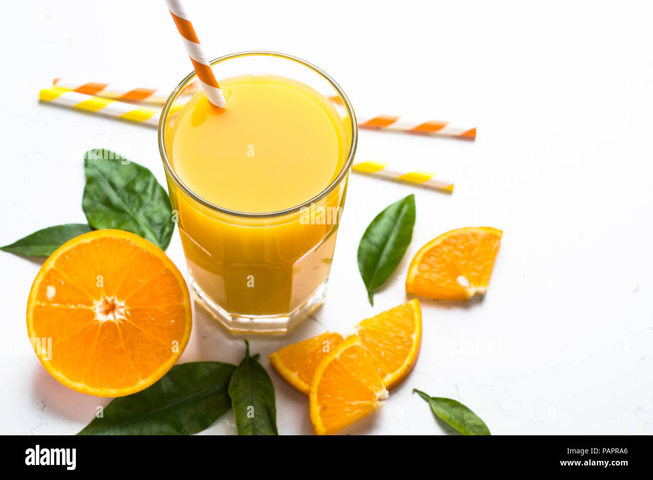 Fresh Orange juice smoothie in glass and sliced citrus around. Healthy drink on white. - Stock Image