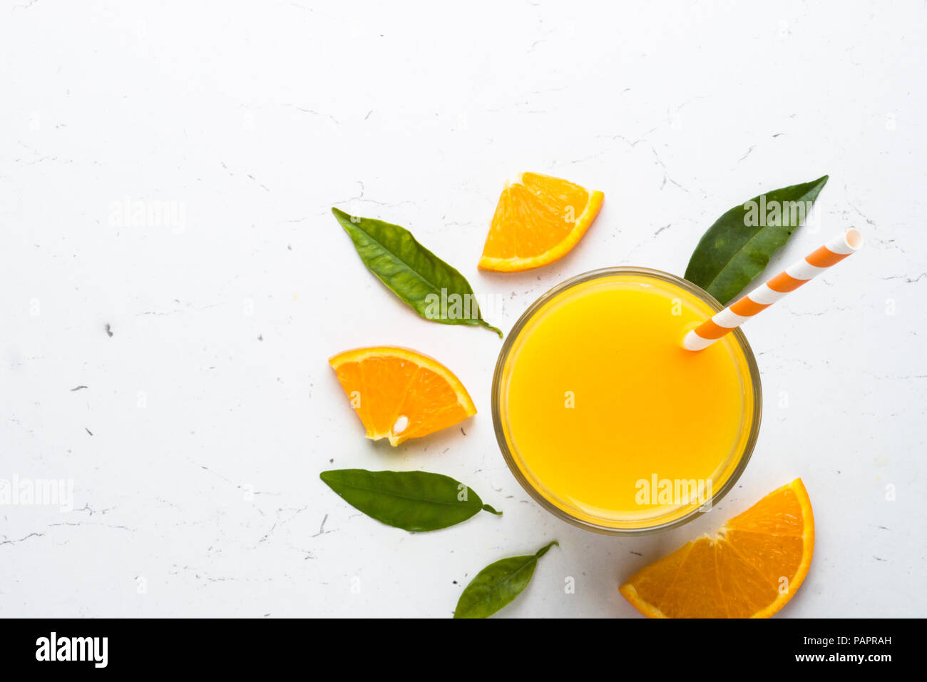 Fresh Orange juice smoothie in glass and fresh citrus around. Healthy drink on white. Top view. - Stock Image