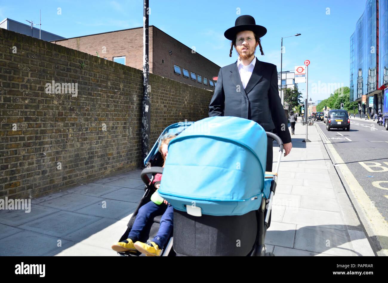 Orthodox / Hasidic Jewish man pushing a double pushchair, London, England, UK. - Stock Image