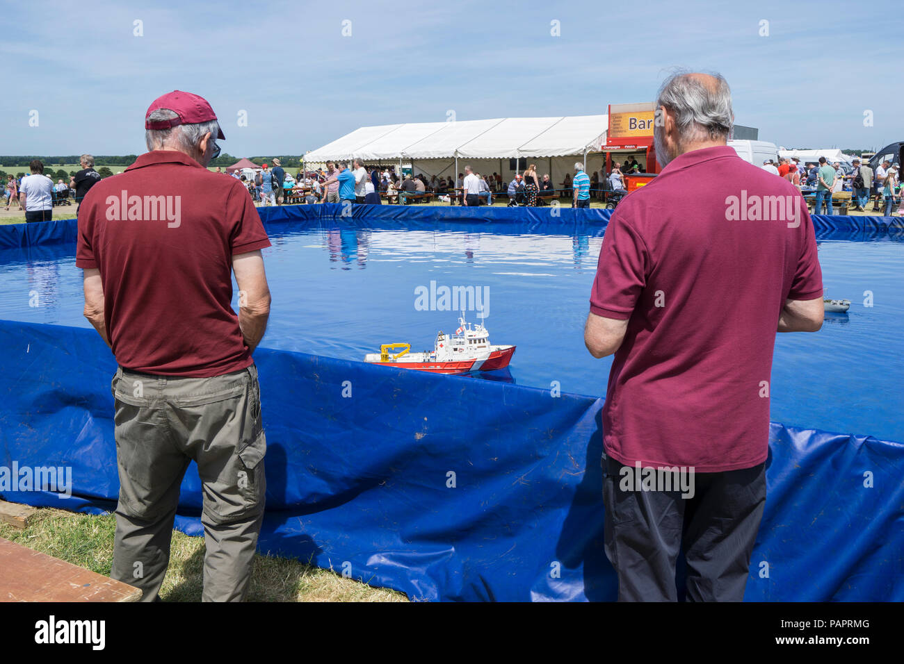 Two model boat enthusiasts controlling models on pool at wings and wheels - Stock Image