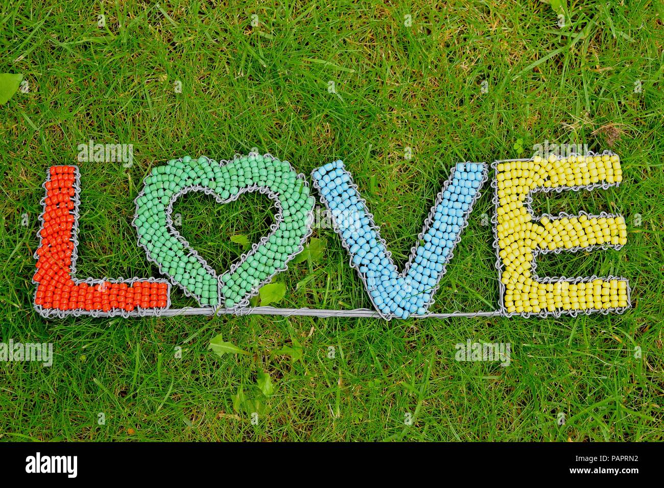 Word love on natural grass background - Stock Image