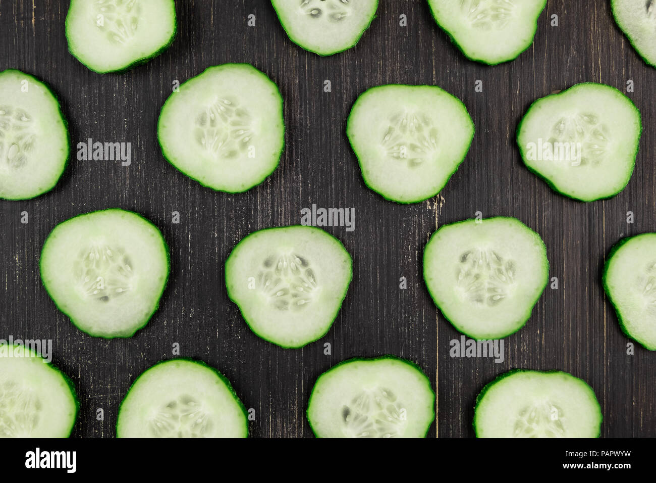 Fresh sliced cucumbers on black wood rustic background, top view. Flat lay pattern of green cucumbers on table, close-up - Stock Image
