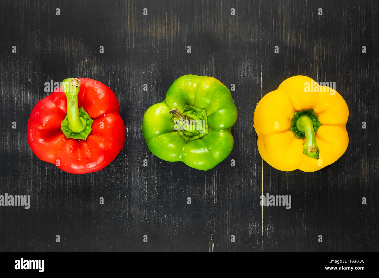 Top view of three fresh bright bell peppers on black rustic background. Shot from above of green, yellow and red paprika vegetables on dark wood table - Stock Image