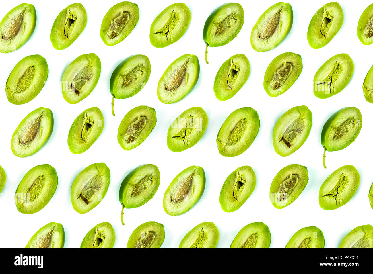 Bright top view pattern of fresh green olives cut in half on white background. Shot from above of multiple olives - Stock Image