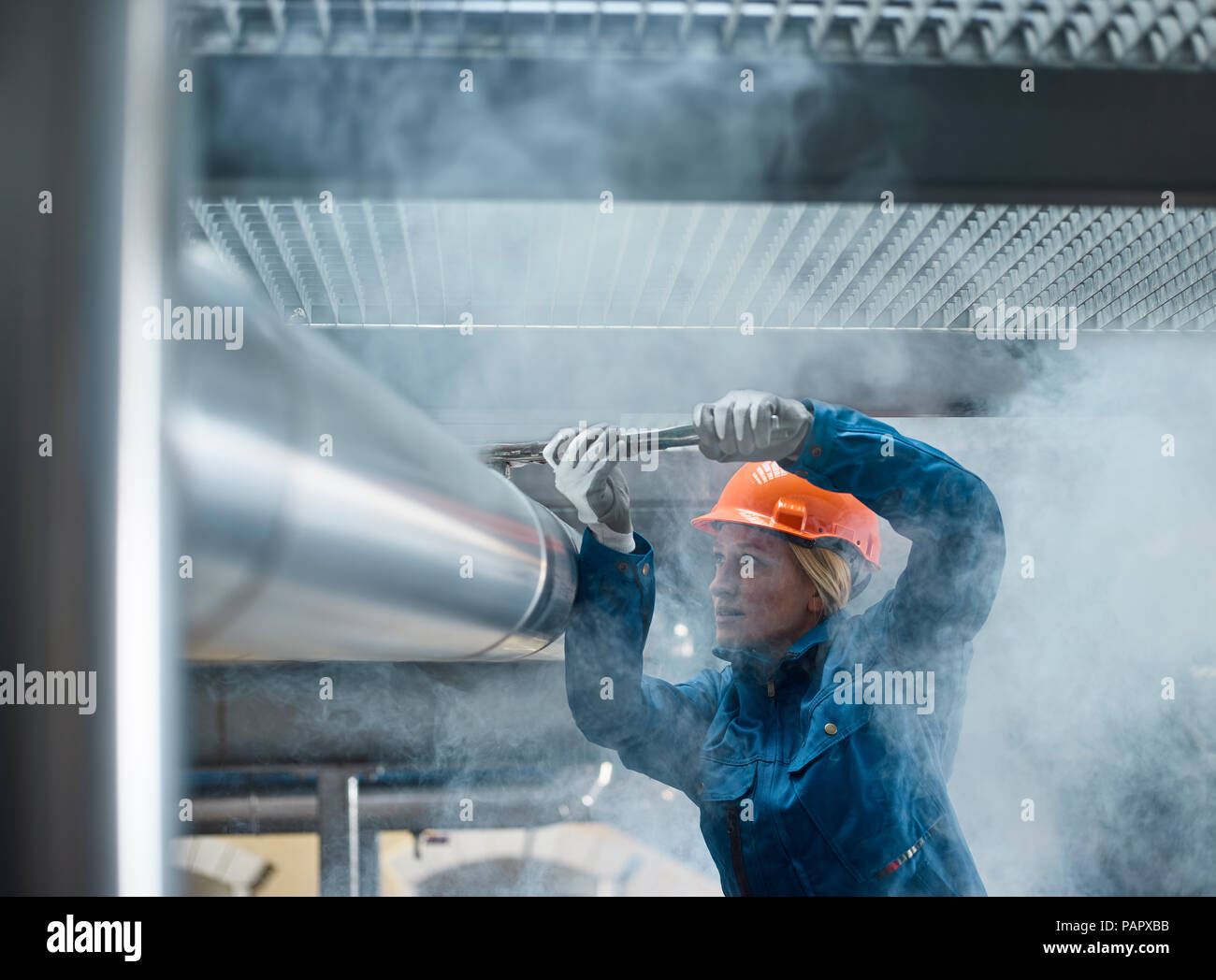 Female mechanic fixing pipework with gaspipe pliers - Stock Image