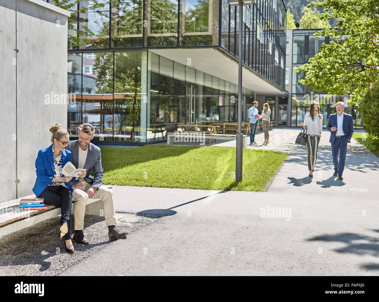 Smiling colleagues with book sitting on bench outside office building - Stock Image