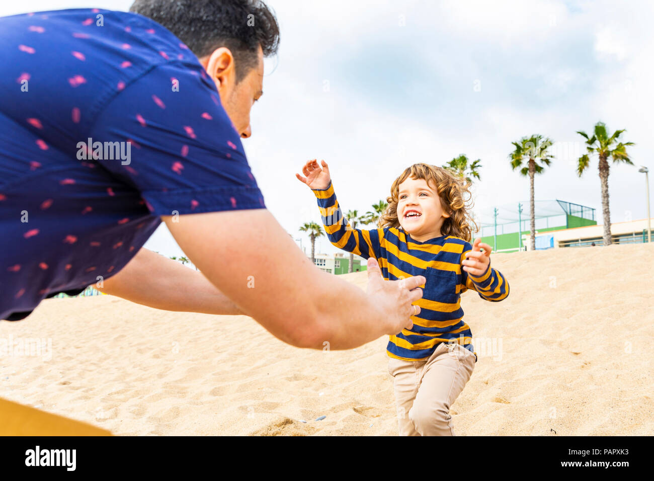 Spain, Barcelona, boy running toward his father on the beach - Stock Image