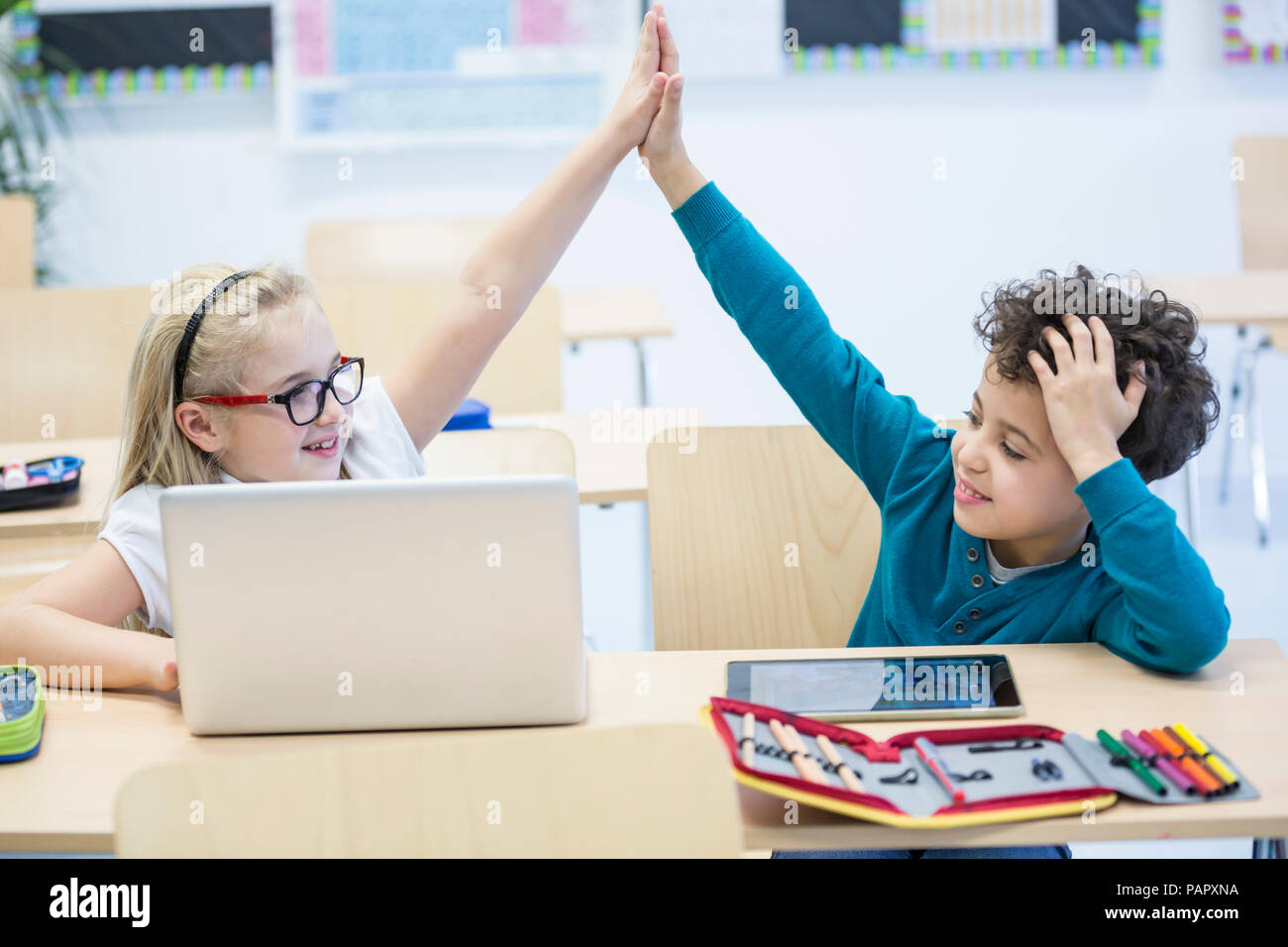 Schoolboy and schoolgirl with laptop high fiving in class - Stock Image