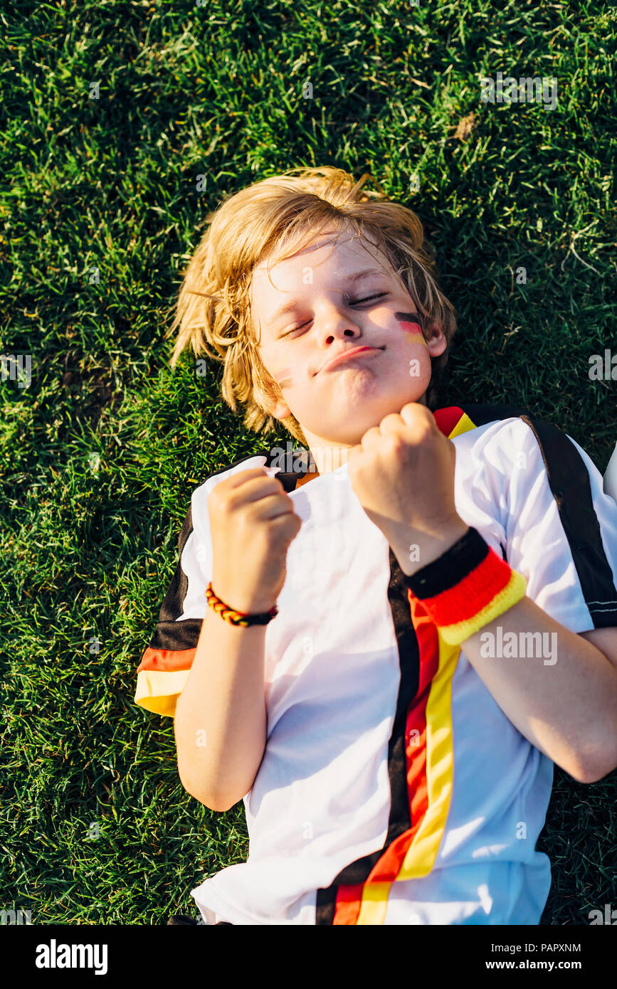 Boy in German soccer shirt lying on grass, keeping fingers crossed for world chamiponship - Stock Image