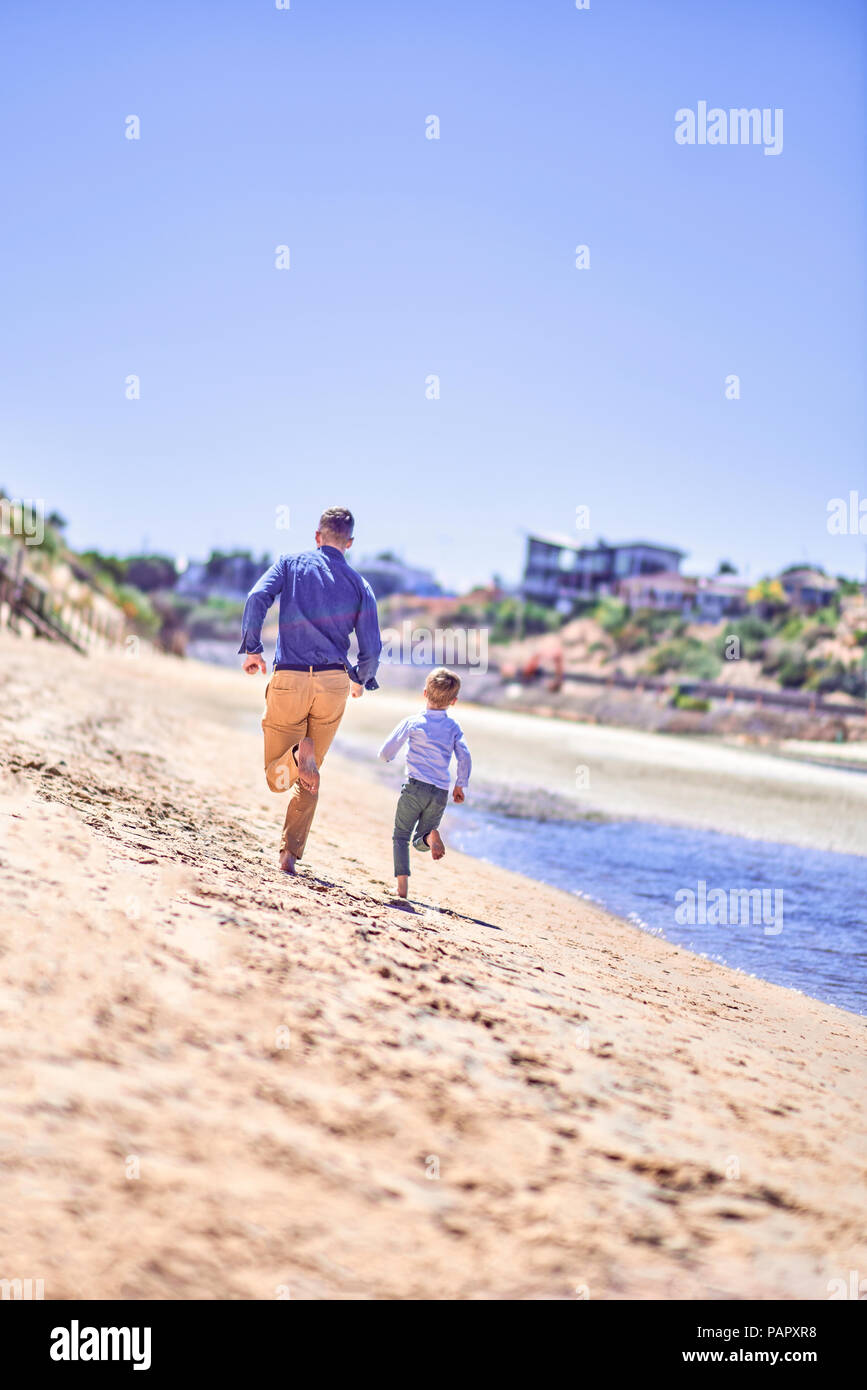 Australia, Adelaide, Onkaparinga River, father and son running on the beach - Stock Image