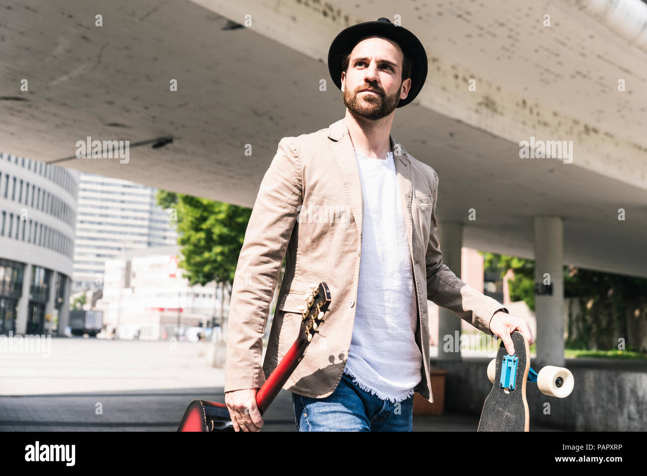 Young man with guitar and skateboard walking in the city - Stock Image