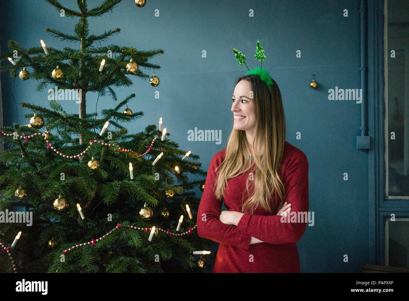 Content woman with Christmas headdress standing besides decorated Christmas tree - Stock Image