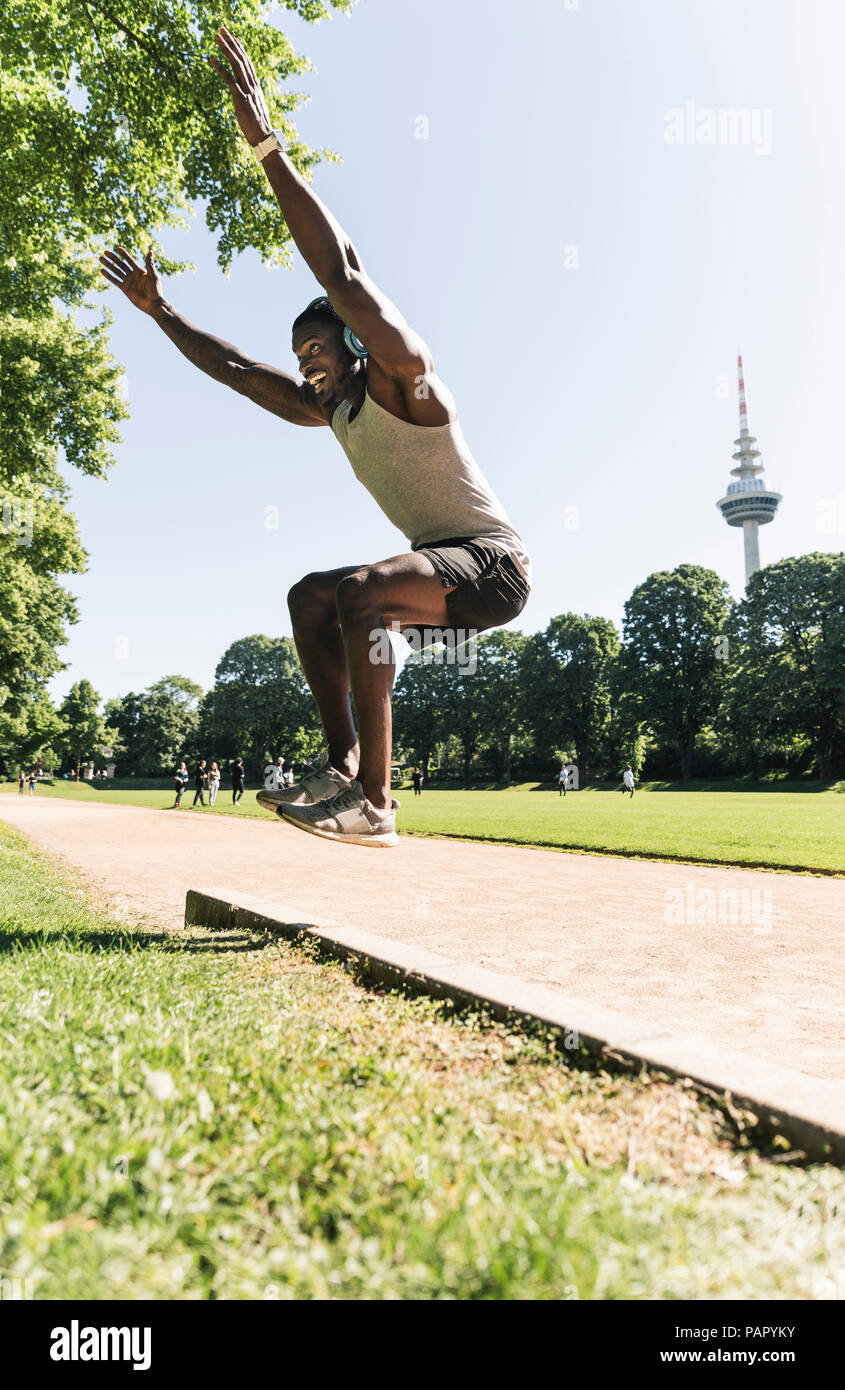 Young athlete with headphones, listening music, training long jump - Stock Image