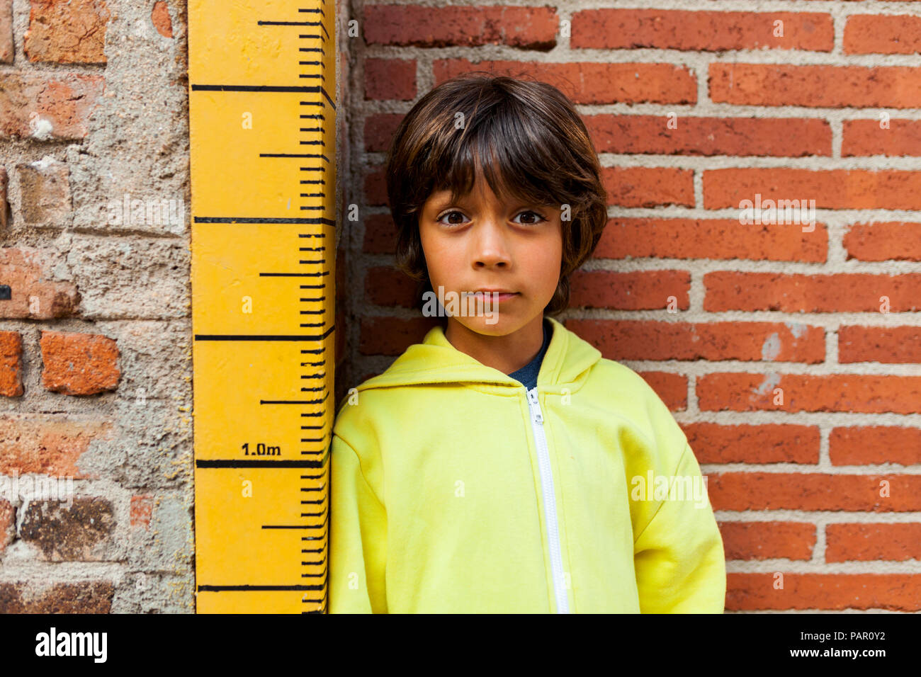 Portrait of sceptical boy leaning against yardstick - Stock Image