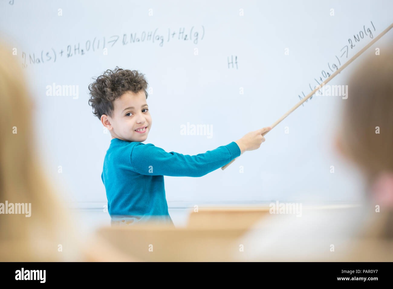 Schoolboy explaining formula at whiteboard in class - Stock Image
