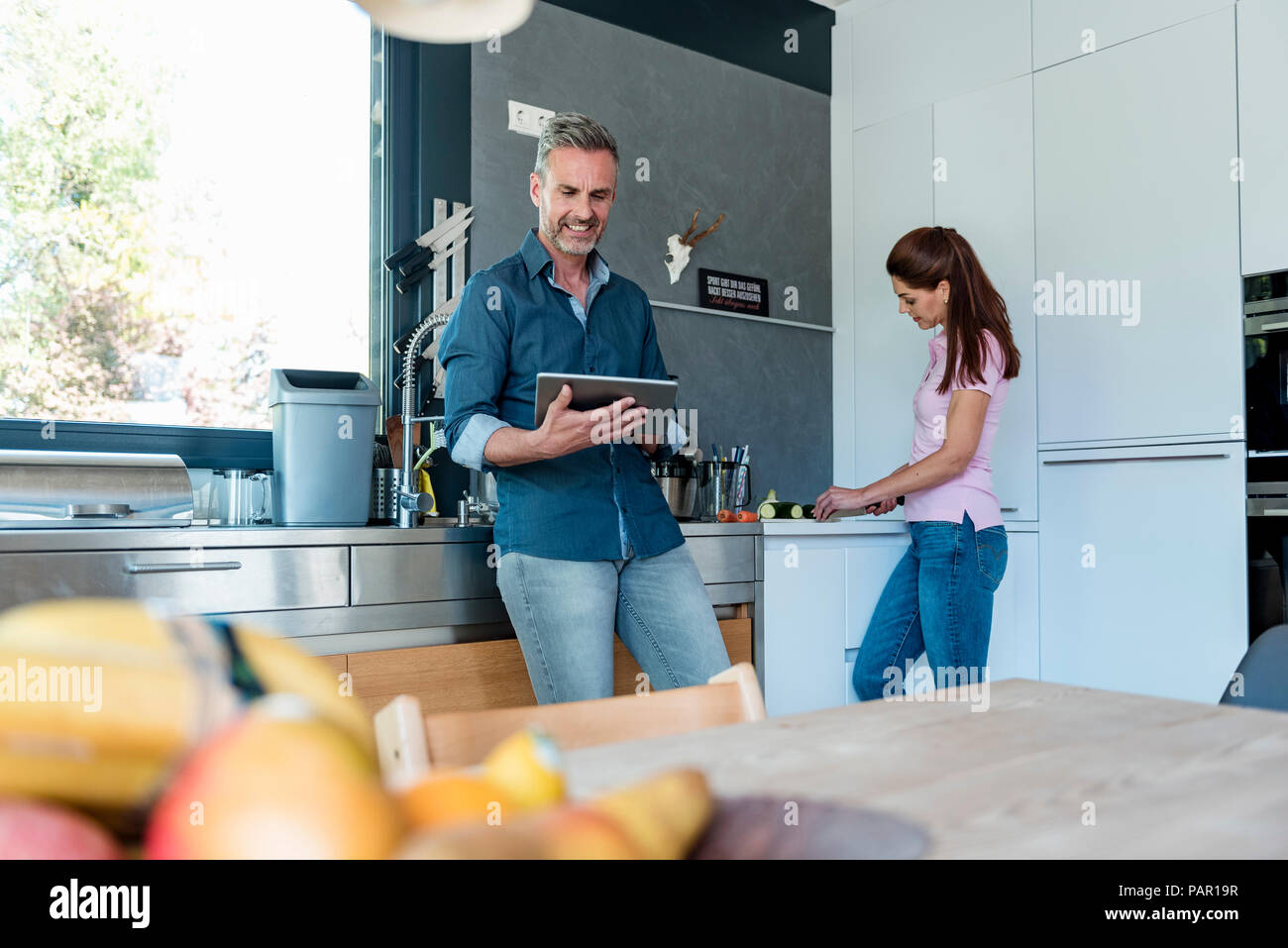 Couple in kitchen at home cooking and using a tablet - Stock Image
