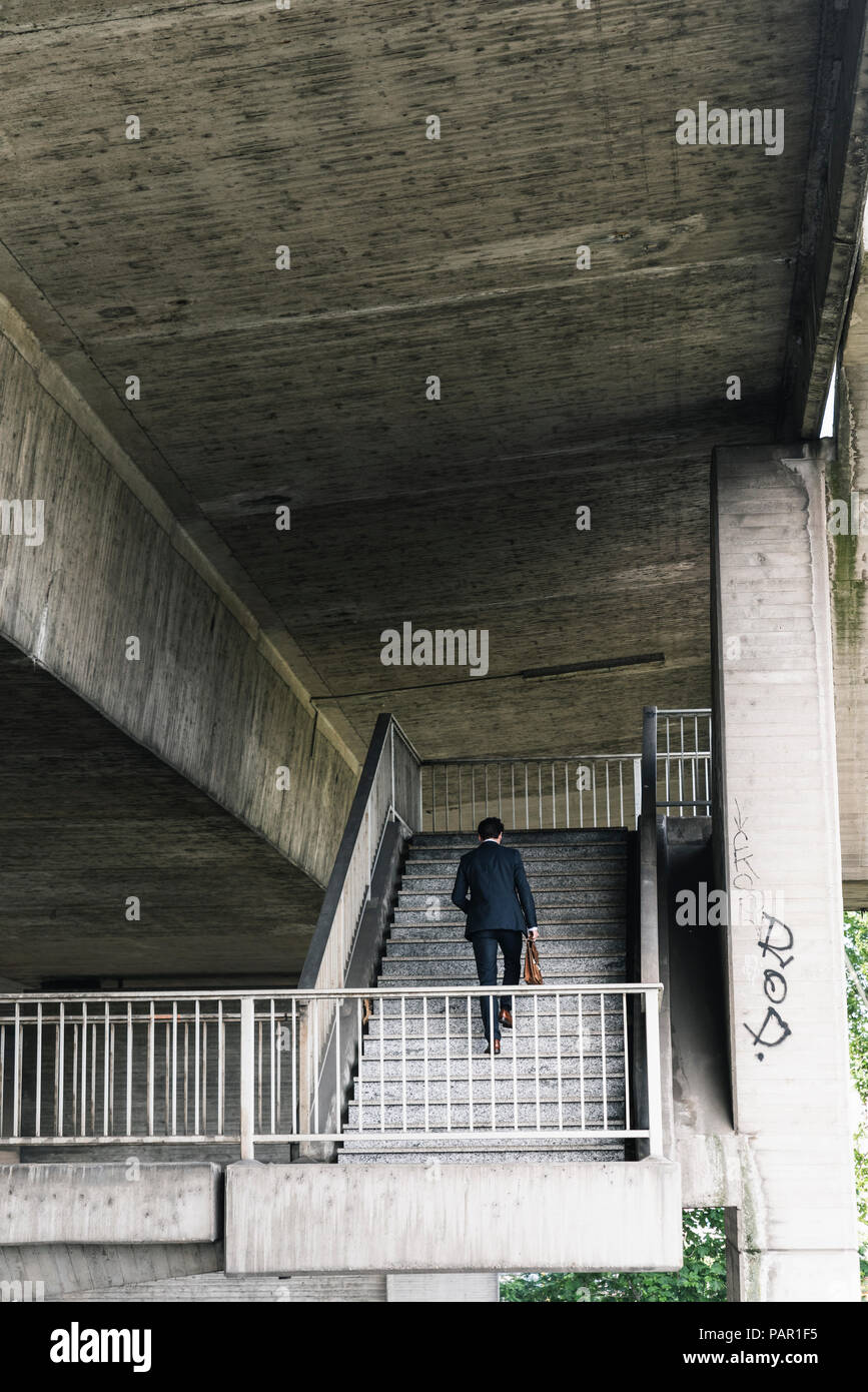 Businessman at underpass walking upstairs Stock Photo