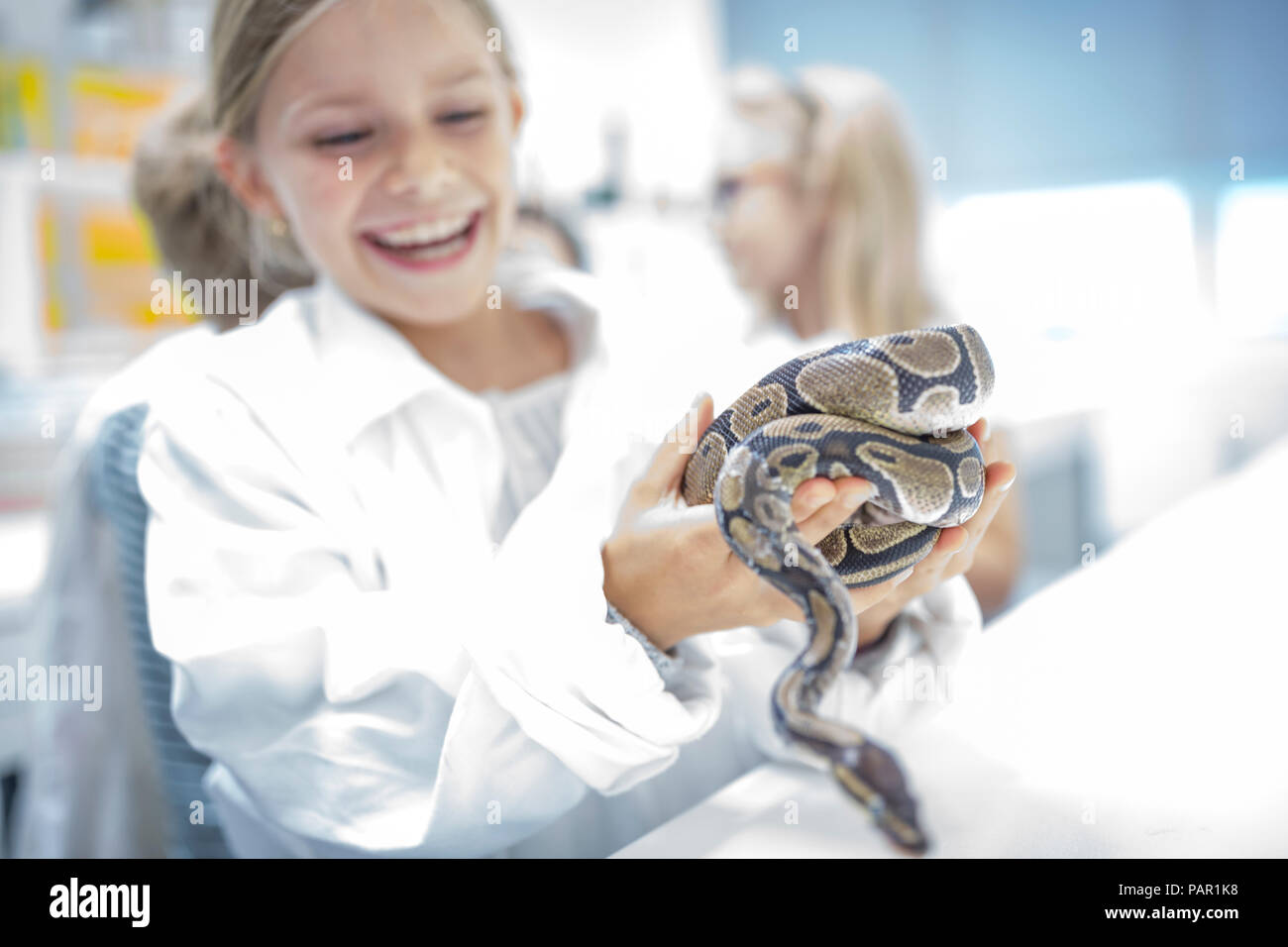 Happy schoolgirl in science class holding snake Stock Photo