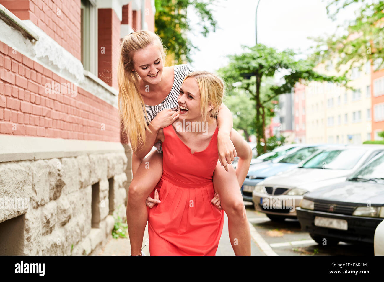 Happy young woman giving friend piggyback ride in the city - Stock Image