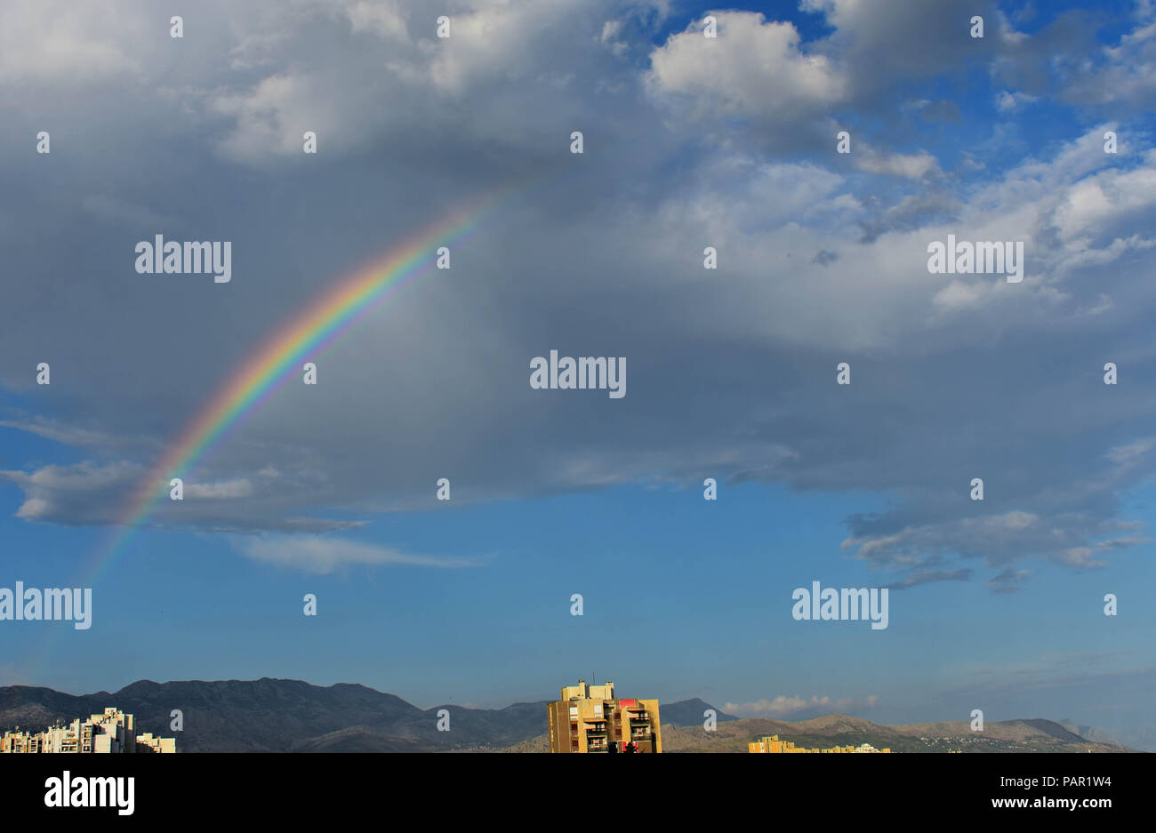Bright colorful rainbow over city, sun shining in rainy day, beautiful colors phenomenon in dark blue sky, overcast weather, nature landscape in the t - Stock Image