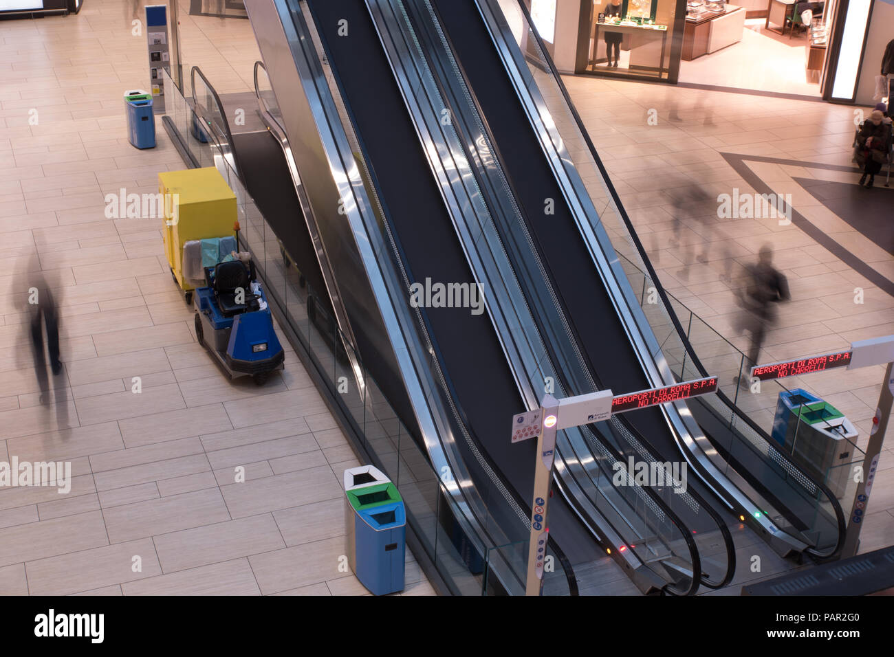 A Long exposure photograph of two escalators in Rome Airport terminal lounge with members of the public zipping past going to and from their flights - Stock Image