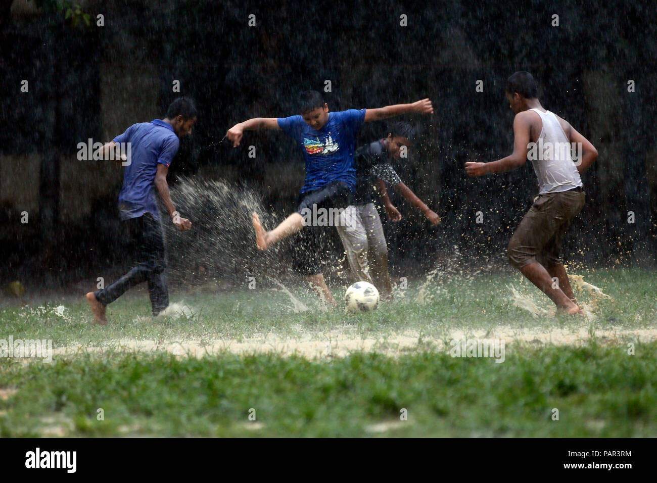 The fiver Continuing:  Jubilates enjoy soccer during rain at Bangabhaban Govt. Primary School ground in The Capital, Dhaka, Bangladesh. July 23, 2018 - Stock Image