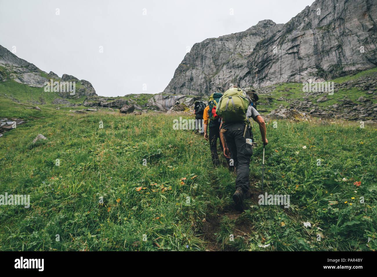 Norway, Lofoten, Moskenesoy, Young men hiking at Horseid Beach - Stock Image
