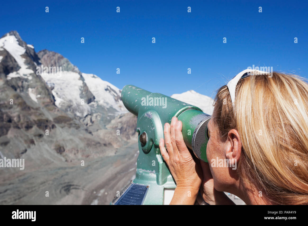 Austria, Carinthia, woman looking through binocular pointing at Grossglockner peak and Pasterze glacier, view from Kaiser-Franz-Josefs-Hoehe - Stock Image