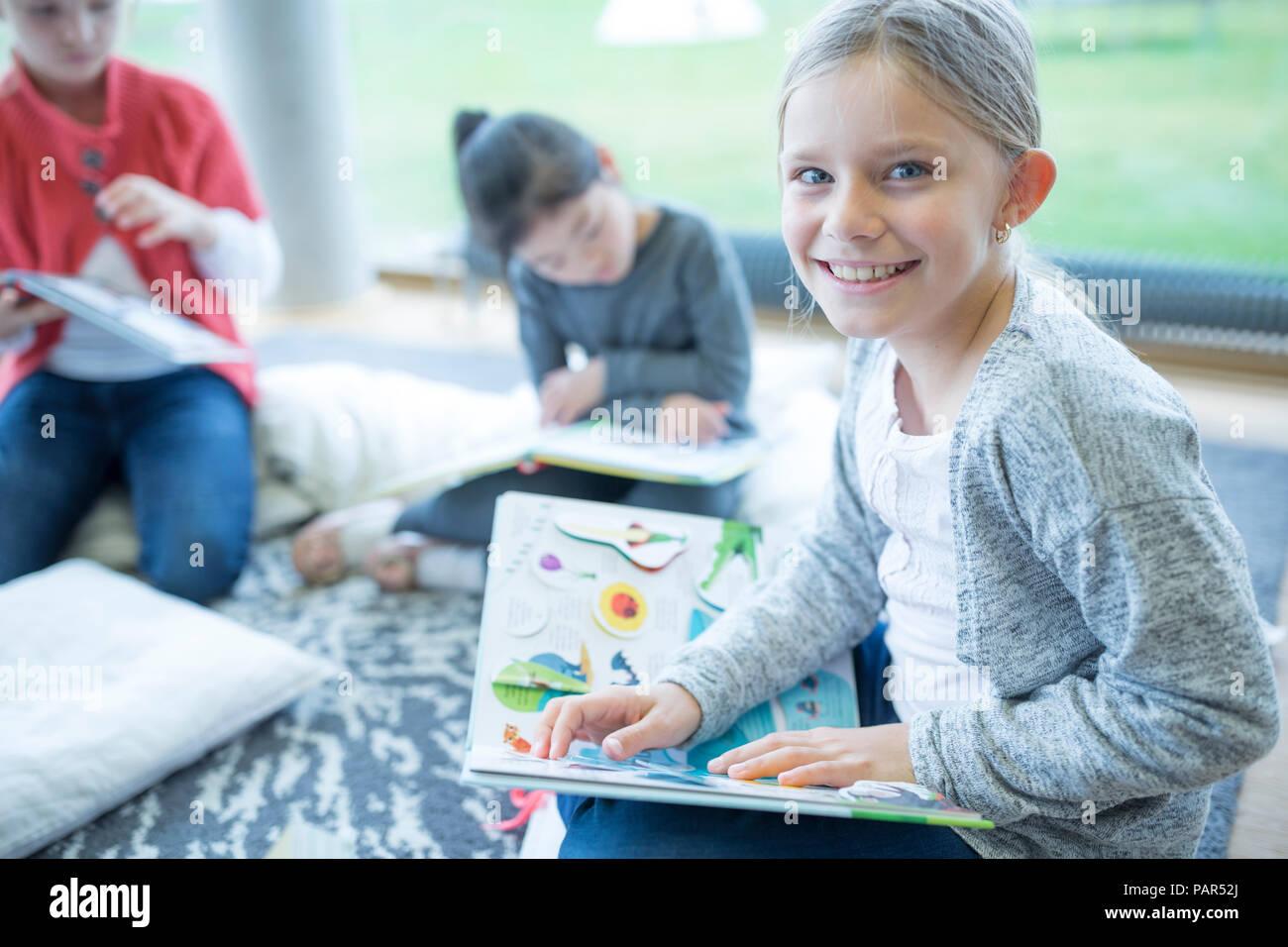 Portrait of smiling schoolgirl sitting on the floor with book in school break room - Stock Image