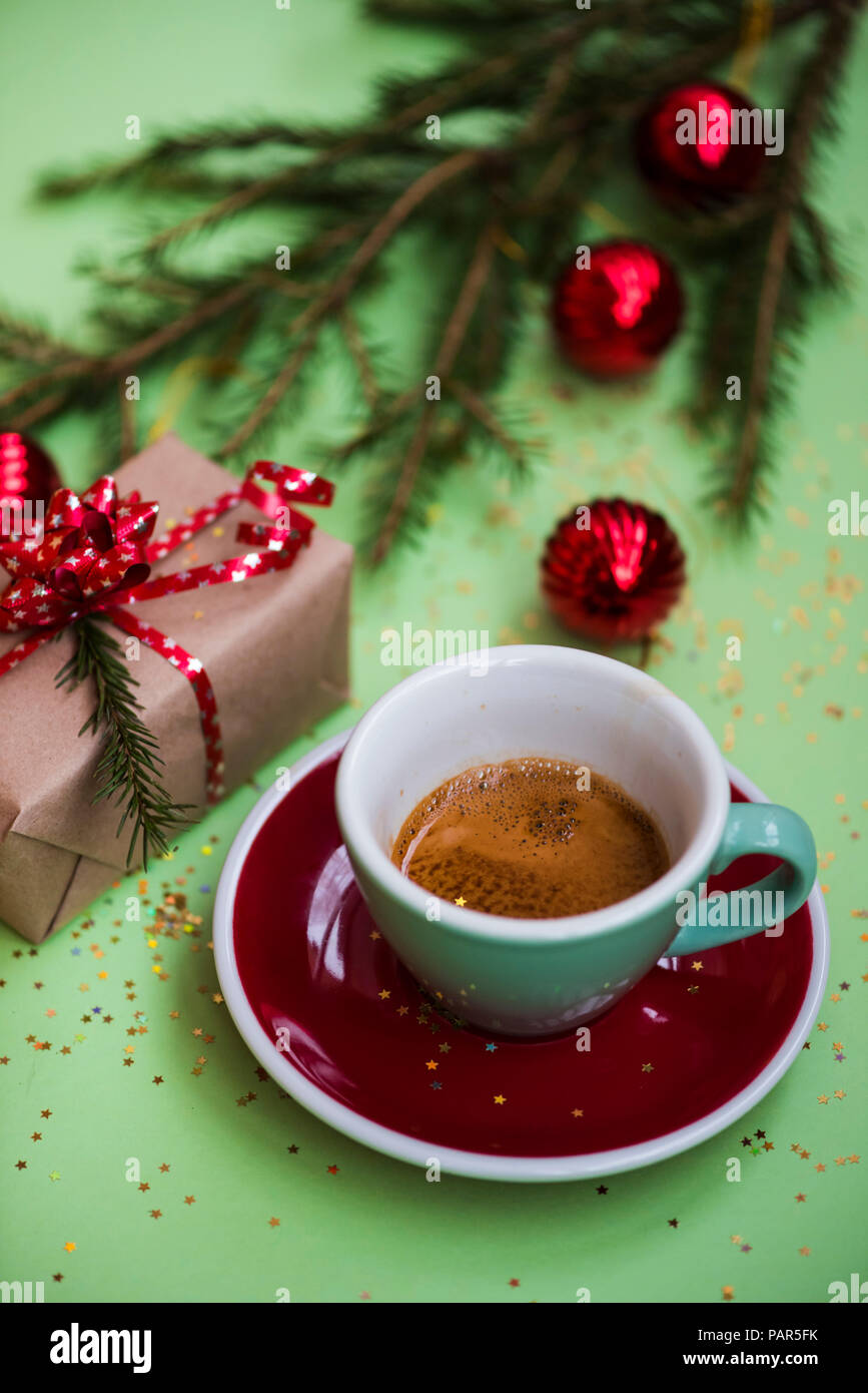 Delicious fresh morning winter festive espresso coffee in a green mug and a red saucer on the green background with christmas decoration - Stock Image