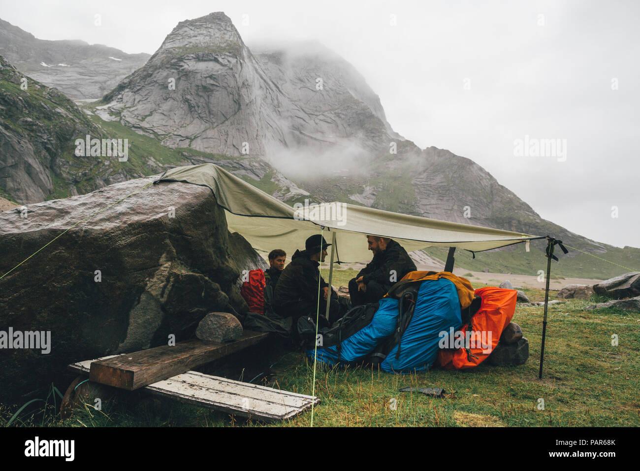Norway, Lofoten, Moskenesoy, Young men camping at Bunes Beach - Stock Image