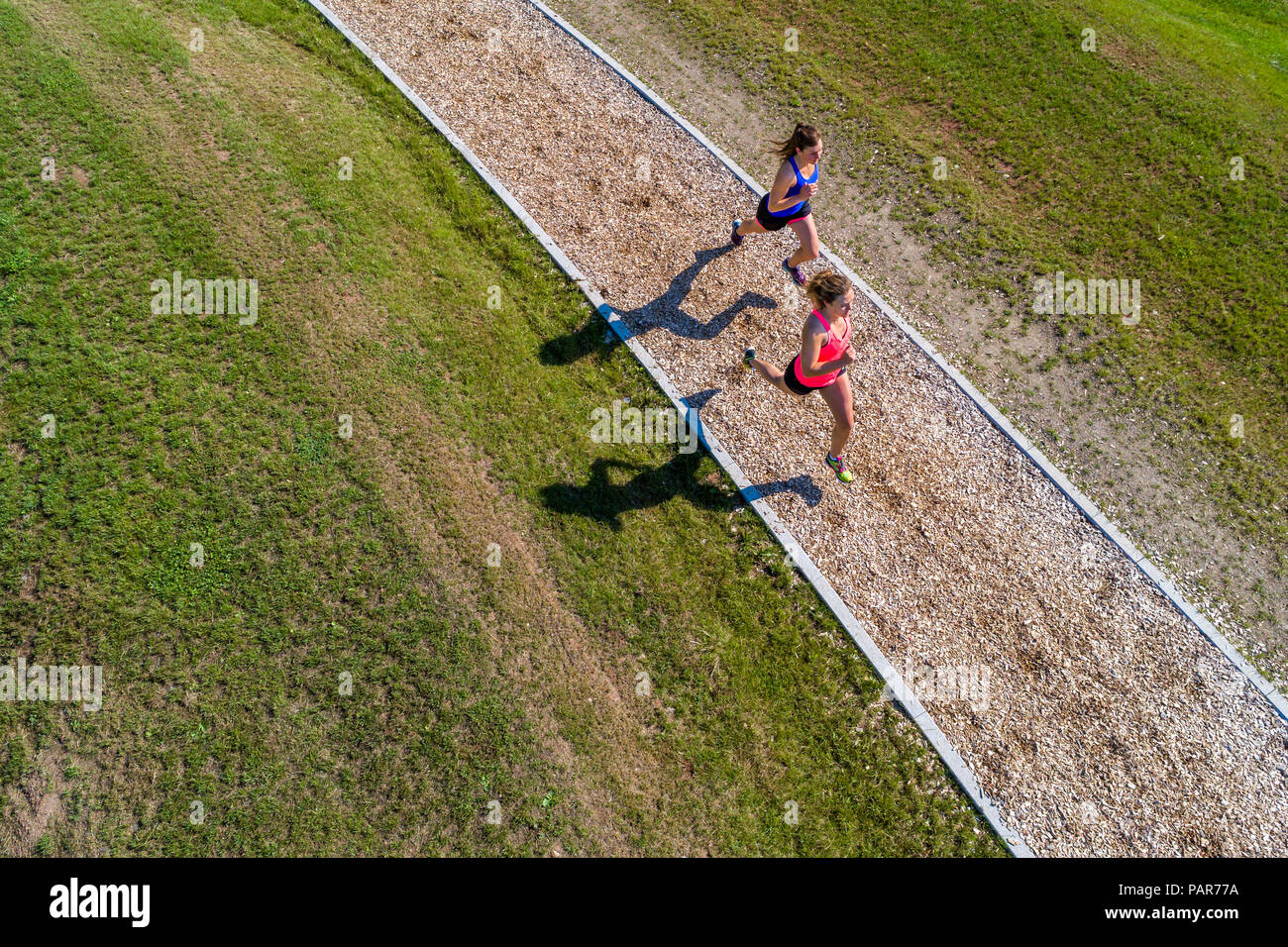 Aerial view of female joggers on woodchip trail - Stock Image