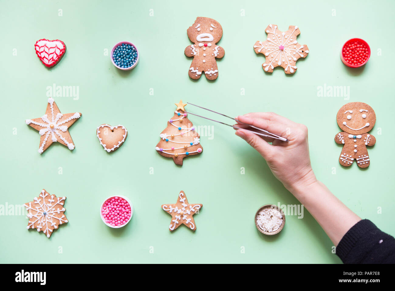 Woman's hand decorating Gingerbread cookies - Stock Image